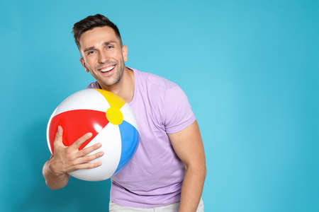 Happy young man with bright inflatable ball on blue background, space for text Imagens