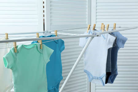 Different cute baby clothes hanging on clothes line indoors. Laundry day