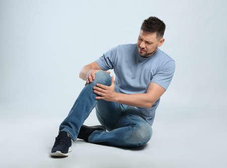 Pełna długość portret mężczyzny z problemami z kolanem, siedzącego na szarym tle