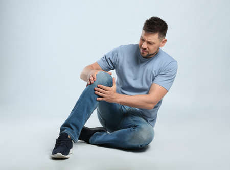 Volledig lengteportret van een man met knieproblemen die op een grijze achtergrond zit