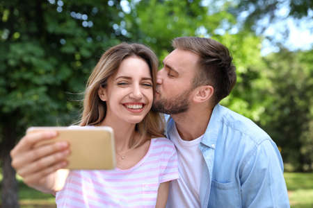 Happy young couple taking selfie in park