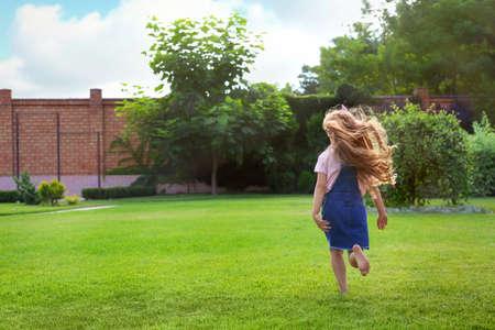 Niña linda corriendo en el parque verde el día de verano
