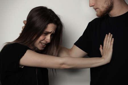 Mężczyzna walczy z kobietą na jasnym tle. Zatrzymaj atak