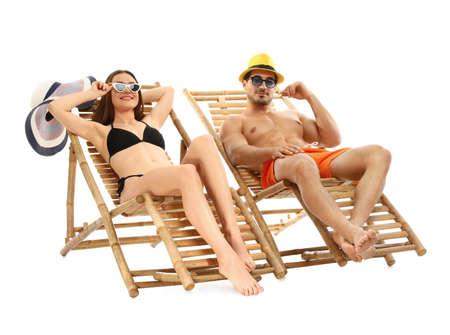 Jeune couple sur des chaises longues sur fond blanc. Accessoires de plage Banque d'images