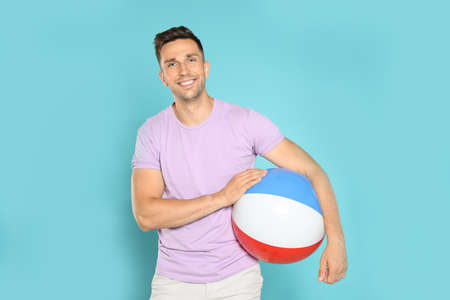 Happy young man with bright inflatable ball on blue background Imagens