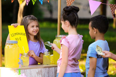 Little girl selling natural lemonade to kids in park. Summer refreshing drink Stockfoto