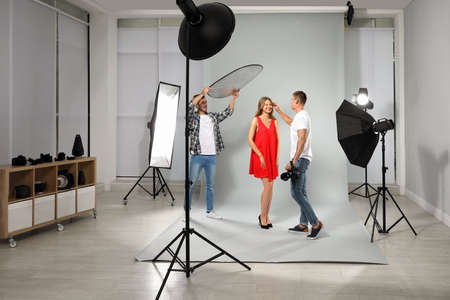 Professional photographer and assistant working with model in modern studio 免版税图像 - 128520315