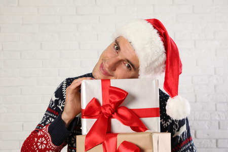 Happy man in Christmas sweater and Santa hat holding gift boxes near white brick wall Stock Photo