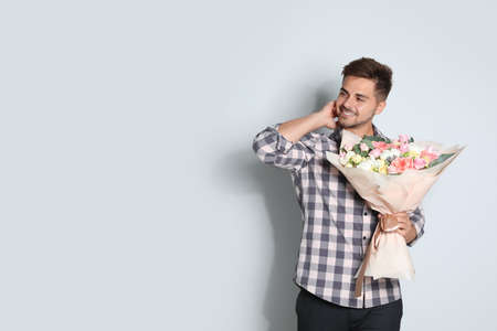 Young handsome man with beautiful flower bouquet on light background, space for text