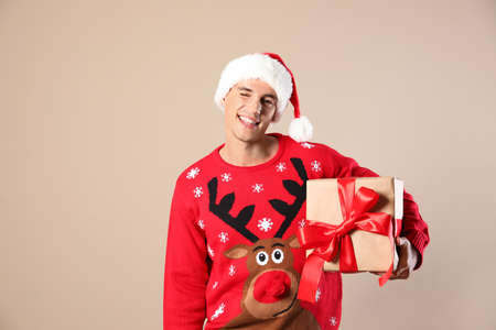 Happy man in Christmas sweater and Santa hat holding gift box on beige background