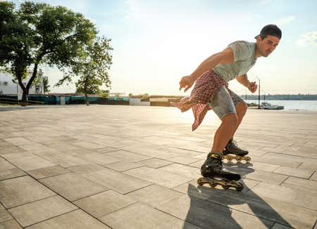 Handsome young man roller skating on pier near river, space for text