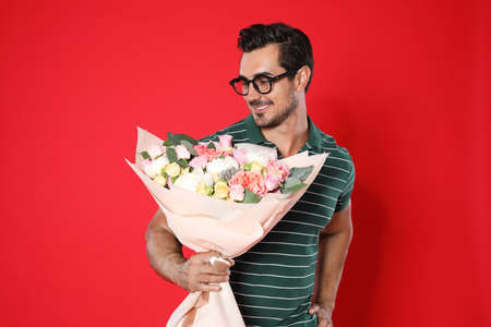 Young handsome man with beautiful flower bouquet on red background