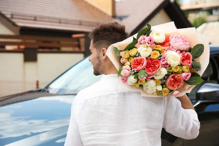 Young man with beautiful flower bouquet near car outdoors
