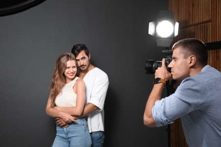Professional photographer taking picture of young couple on dark grey background in modern studio 版權商用圖片