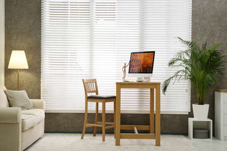 Comfortable workplace near window with blinds in room 免版税图像