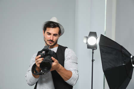 Professional photographer with modern camera in studio Banco de Imagens