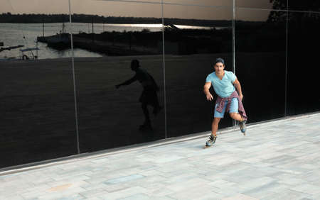 Handsome young man roller skating near glass building on city street, space for text