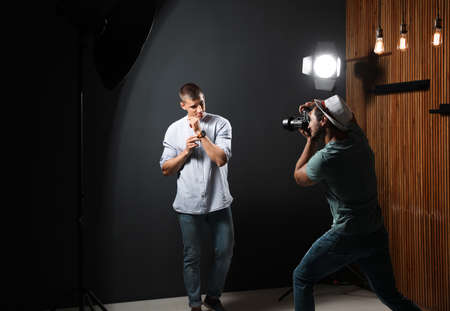Professional photographer taking picture of young man on dark grey background in modern studio