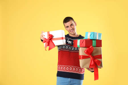 Happy man in Christmas sweater holding gift boxes on yellow background Stock Photo