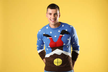 Portrait of happy young man in Christmas sweater on yellow background
