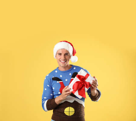 Happy man in Christmas sweater and Santa hat holding gift box on yellow background