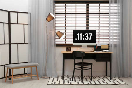 Comfortable workplace near window with blinds in room Фото со стока