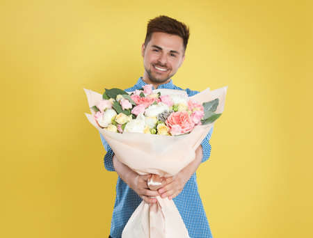 Young handsome man with beautiful flower bouquet on yellow background