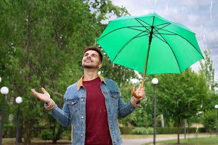 Man with umbrella outdoors on rainy day