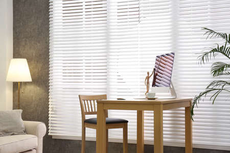 Comfortable workplace near window with blinds in room Reklamní fotografie