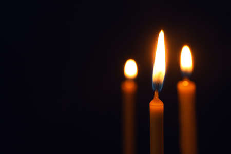 Burning candles on dark background, space for text. Symbol of sorrow Imagens