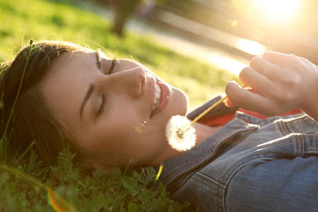 Young woman with dandelion in park on sunny day. Allergy free concept