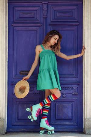 Happy girl with retro roller skates standing near violet door