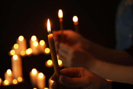Woman holding burning candle in darkness against blurred background, closeup