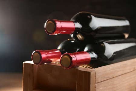 Wooden crate with bottles of wine on dark background, closeup