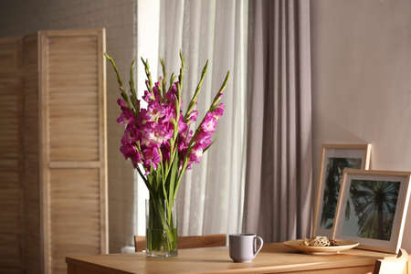 Vase with beautiful pink gladiolus flowers, pictures and cup on wooden table in room, space for text