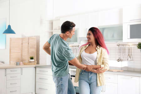Beautiful couple dancing in kitchen at home