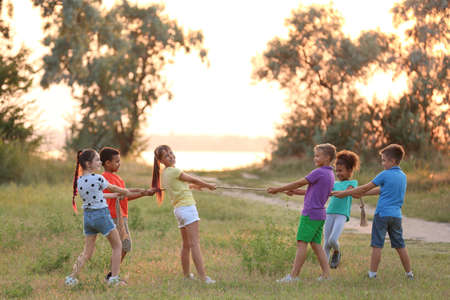 Cute little children playing outdoors at sunset