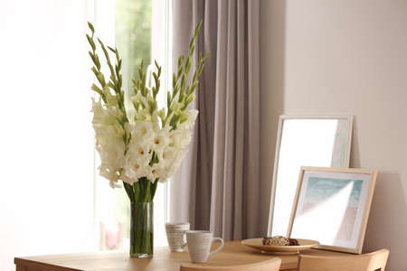 Vase with beautiful white gladiolus flowers, pictures and cups on wooden table in room, space for text