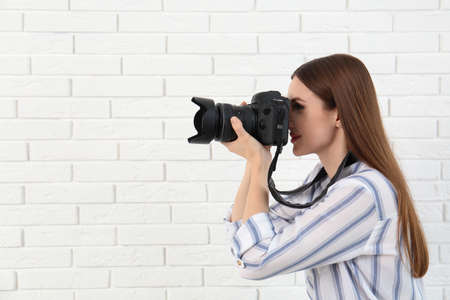 Professional photographer taking picture near white brick wall