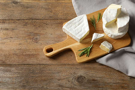 Wooden board with delicious cheeses on table, above view. Space for text