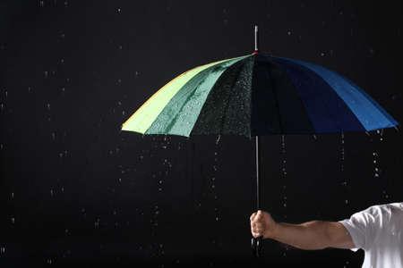 Hombre sujetando paraguas de color bajo la lluvia sobre fondo negro, primer plano Foto de archivo