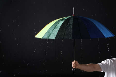 Man holding color umbrella under rain against black background, closeup