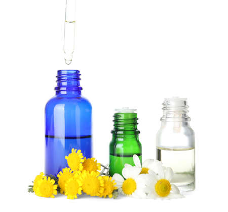 Dropping herbal essential oil into bottle and flowers isolated on white