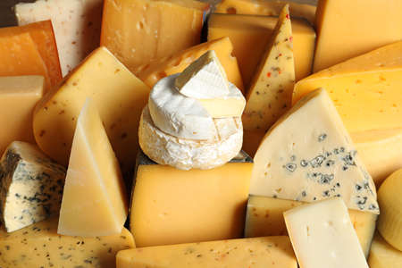 Different types of delicious cheese as background, closeup