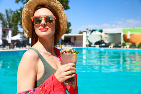 Young woman with cocktail relaxing at swimming pool on sunny day. Space for text Imagens