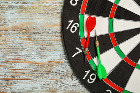 Dart board with arrows on color wooden background, top view. Space for text 写真素材