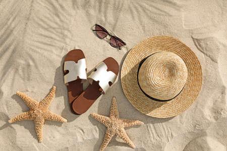 Composición plana con accesorios de playa sobre arena. Foto de archivo