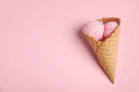 Delicious ice cream in wafer cone on pink background, top view. Space for text Foto de archivo