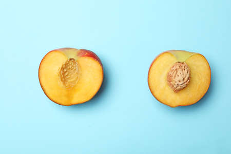 Halves of sweet juicy peach on light blue background, top view 写真素材