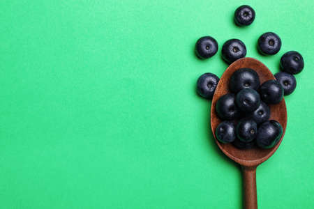 Fresh acai berries with wooden spoon on green background, flat lay. Space for text